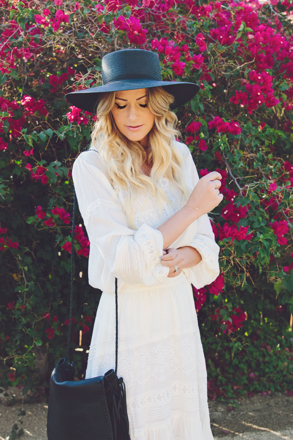 Dash of Darling wears a white Spell & The Gypsy Collective Byron Bay top and skirt with a Janessa Leone straw boater hat and a Jennifer Haley fringe bag while in Palm Springs staying at the Korakia Pensione hotel.
