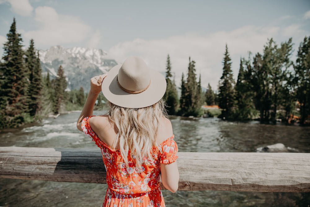 Dash of Darling shares an off shoulder orange dress in Jackson Hole, Wyoming while 21 weeks pregnant.