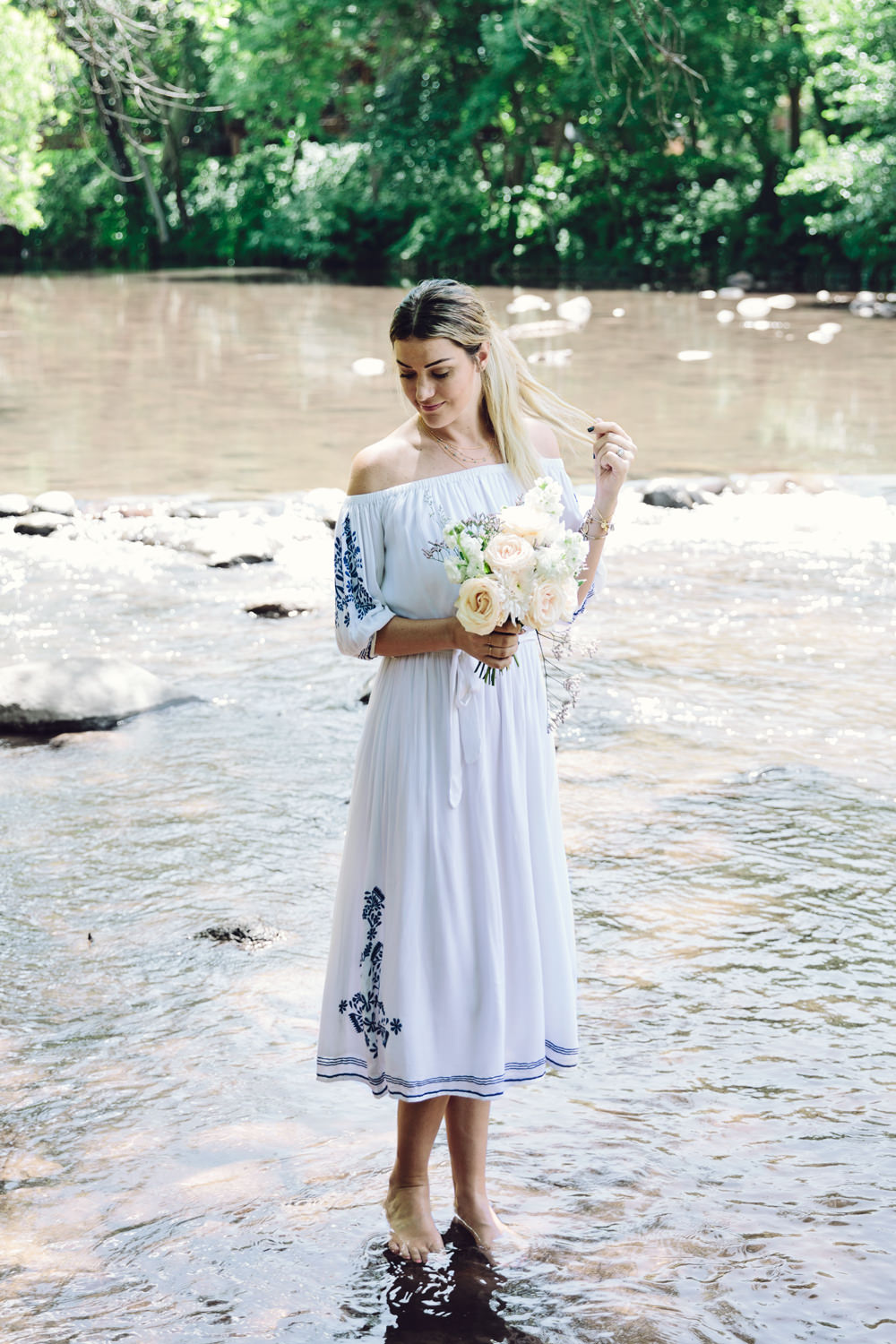 Dash of Darling wears a Tularosa off-shoulder white embroidered midi dress while on vacation in Sedona, Arizona and reviewing Philosophy shower gel for QVC.
