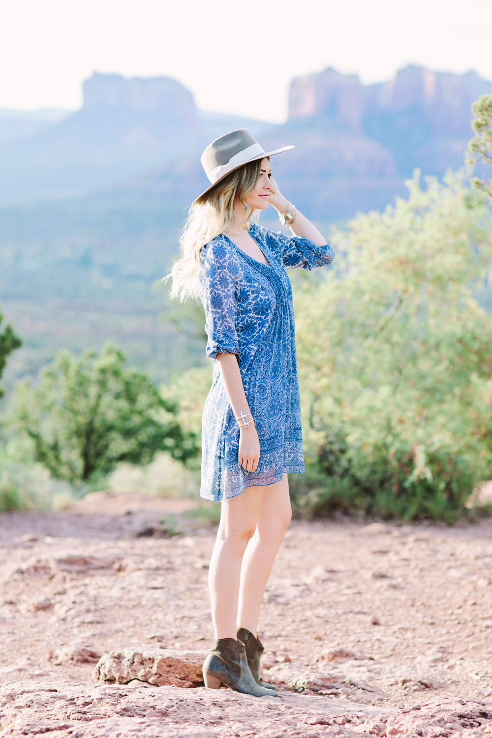 Caitlin Lindquist of the travel blog Dash of Darling styles a summer outfit consisting of a Joie silk shift dress with a Hat Attack felt fedora while exploring the desert in Sedona.