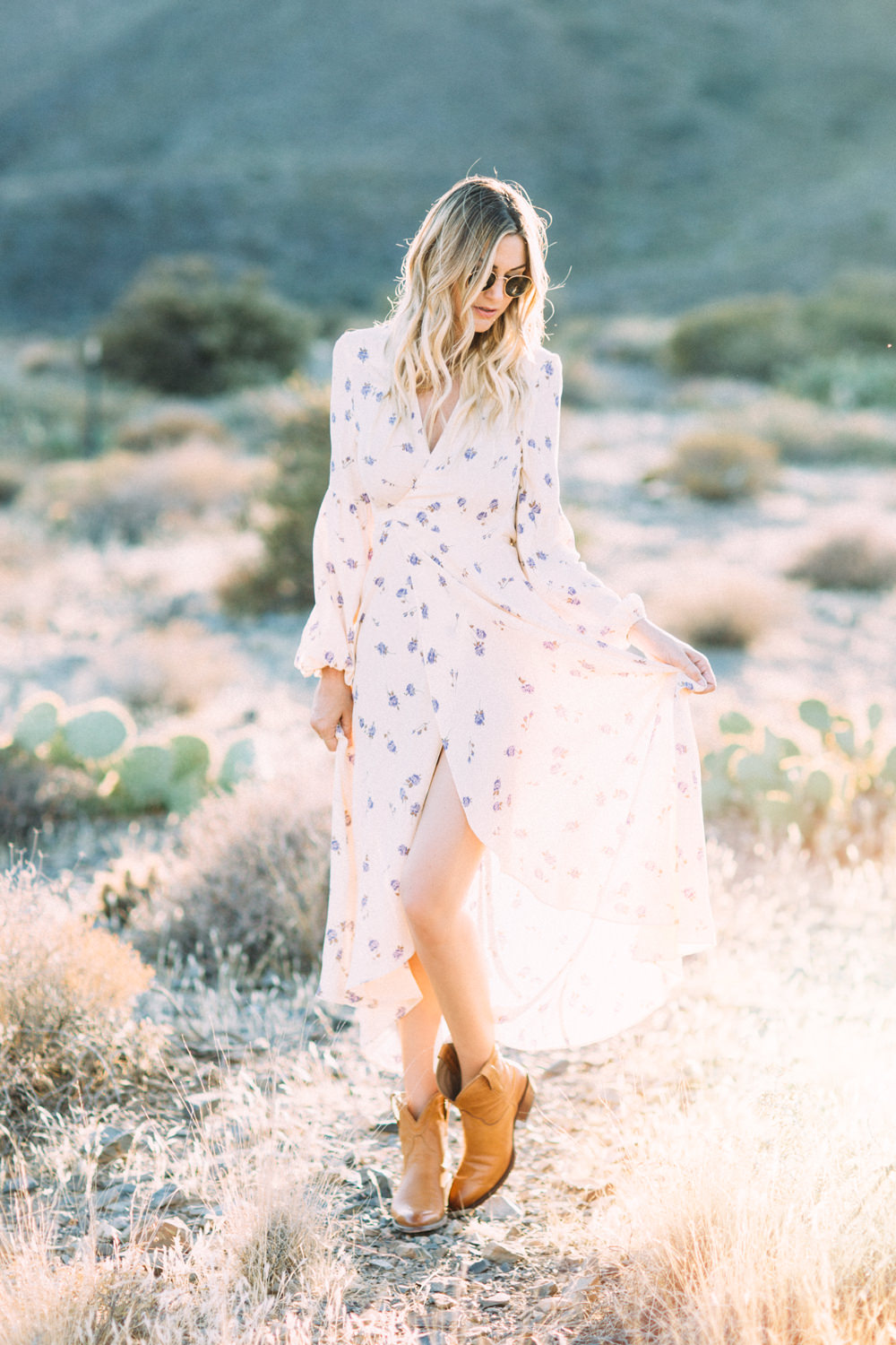 Caitlin Lindquist of Dash of Darling styles a romantic feminine Christy Dawn dress with Tecovas cowgirl boots in the desert.