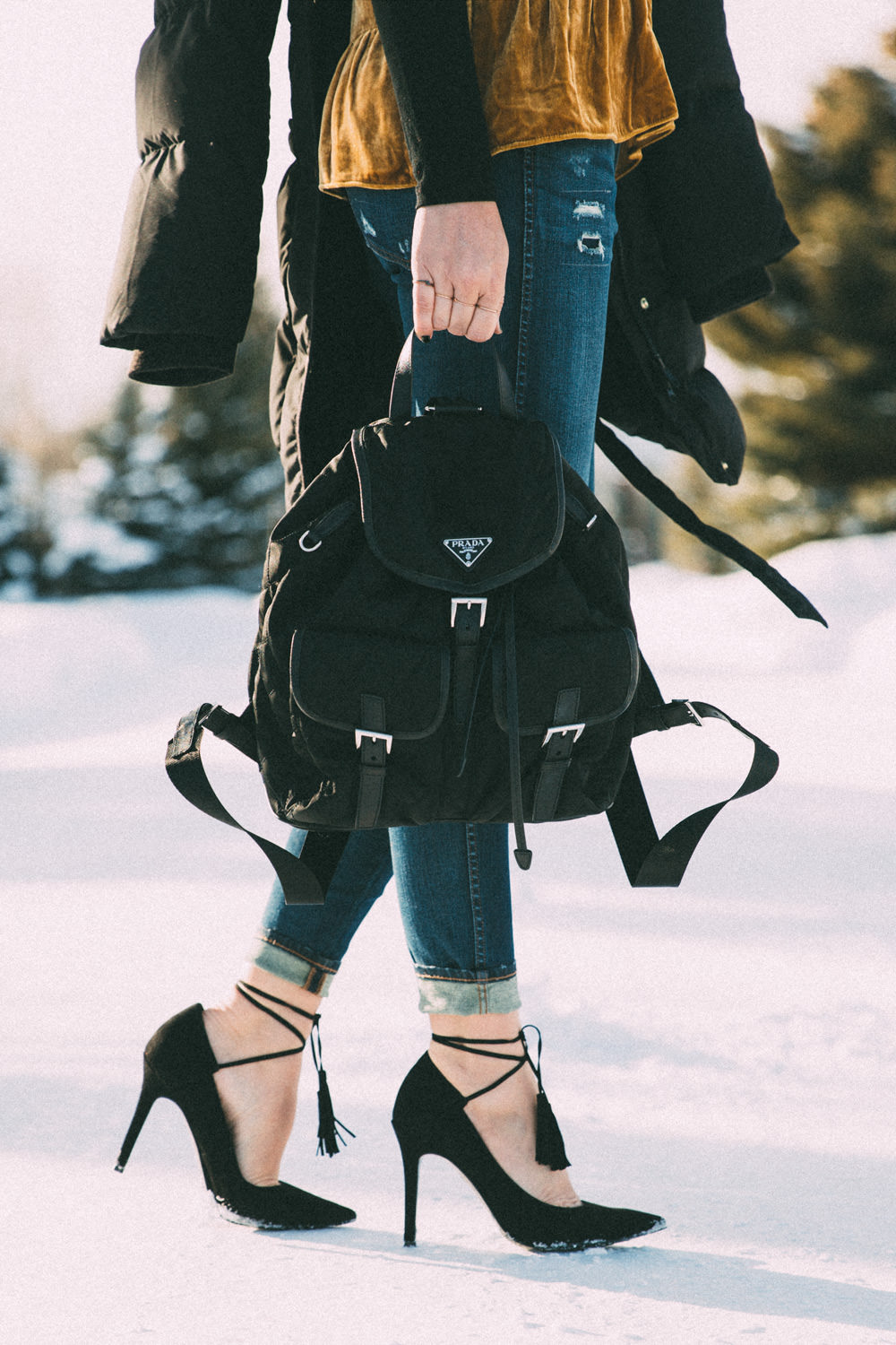 Caitlin Lindquist of Dash of Darling shares a winter outfit in Jackson Wyoming wearing a velvet camisole tank top and madewell ripped high rise skinny denim.